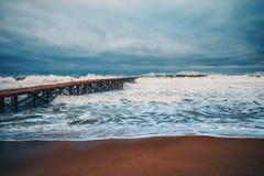 Puente roto viejo en el mar y ondas enormes en el mar profundo fotos de archivo