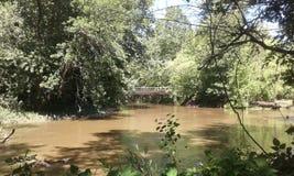 Puente sobre el agua fangosa fotografía de archivo libre de regalías