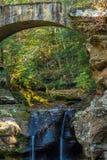 Puente sobre el pequeño río con la cascada en bosque Fotos de archivo
