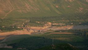 Puente sobre el río bajo en las montañas almacen de metraje de vídeo