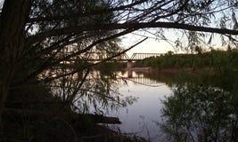 Puente sobre el Red River en la puesta del sol Imágenes de archivo libres de regalías