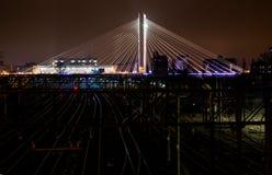 Puente suspendido iluminado sobre la señal moderna urbana ferroviaria
