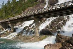 Puente a través de una cascada Imagen de archivo libre de regalías