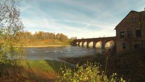 Puente viejo del ladrillo a través del río Venta en la ciudad del vídeo del timelapse de Kuldiga Letonia almacen de video