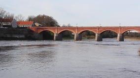 Puente viejo del ladrillo a través del río Venta en la ciudad del vídeo del timelapse de Kuldiga Letonia metrajes