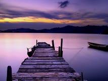 Puente y bote pequeño de madera del pie en la puesta del sol Fotos de archivo libres de regalías