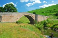 Puente y corriente viejos cerca de Wooler, Northumberland imagen de archivo