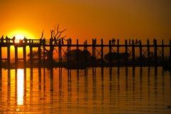 Puente y gente de U Bein en la puesta del sol Foto de archivo libre de regalías