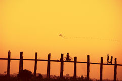 Puente y gente de U Bein en la puesta del sol Fotografía de archivo libre de regalías