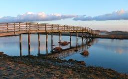 Puente y nubes del bacalao de cabo en la puesta del sol Foto de archivo