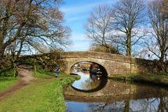 Puente y reflexión del canal con el caminante en camino de sirga Imágenes de archivo libres de regalías