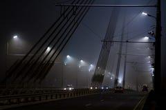 Puente y tráfico debajo de las linternas en la niebla Fotos de archivo libres de regalías