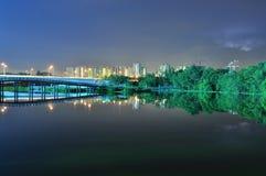 Puentes y verdor por el río en la noche Foto de archivo