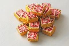Puer te Kuber och briketter av bevarat svart te Puer Shu Puer Puer te i den guld- folien royaltyfri bild