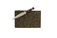 Puerh茶砖和刀子(被隔绝) 免版税库存照片