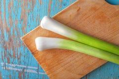 Puerro verde fresco en la tabla de cocina, visión superior Imagenes de archivo