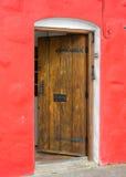 Puerta abierta de madera vieja y pared roja fotos de archivo