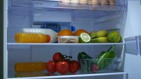 Puerta abierta del refrigerador de la cocina de la mano del hombre que mira dentro para la comida fresca y la bebida almacen de metraje de vídeo