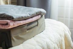 Puerta abierta y maleta abierta con ropa en la cama Fotografía de archivo libre de regalías