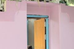 Puerta amarilla aislada de una casa violeta y azul imagenes de archivo