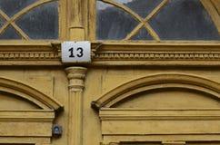 Puerta amarilla vieja con 13 Foto de archivo