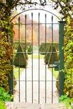Puerta antigua del hierro con el jardín ornamental más allá Fotografía de archivo