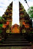 Puerta antigua roja de la piedra a un templo sagrado en Ubud, Bali para que gente ruegue y adore imagen de archivo