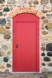 Puerta arqueada rojo brillante en una pared de piedra Imagen de archivo libre de regalías