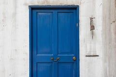 Puerta azul antigua y campana vieja en la pared Fotografía de archivo