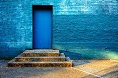 Puerta azul con la pared de ladrillo azul Fotos de archivo libres de regalías