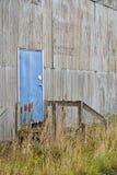 Puerta azul con la pintada en almacén abandonado Fotografía de archivo libre de regalías