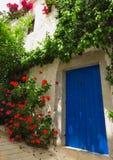 Puerta azul con las flores en pueblo griego mediterráneo Imágenes de archivo libres de regalías