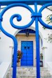 Puerta azul de las barras en el patio blanco Fotografía de archivo