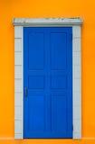 Puerta azul del vintage en pared amarilla brillante Foto de archivo libre de regalías