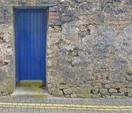 Puerta azul en una pared de piedra Imágenes de archivo libres de regalías