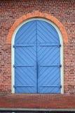 Puerta azul grande del carro en una pared de ladrillo roja Fotos de archivo libres de regalías