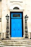 Puerta azul y la fachada clásica con las lámparas del metal Imagenes de archivo