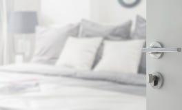Puerta blanca abierta al beddroom con la almohada blanca y gris en cama Imágenes de archivo libres de regalías