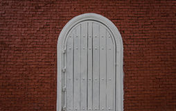 Puerta blanca arqueada en pared de ladrillo roja imágenes de archivo libres de regalías