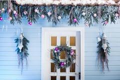 Puerta blanca con la guirnalda de la Navidad de la ejecución debajo del tejado tejado Foto de archivo libre de regalías