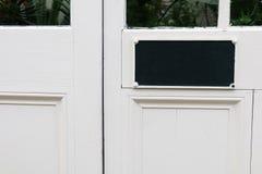 Puerta blanca con la muestra en blanco negra Imagen de archivo