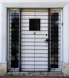 Puerta blanca detrás de barras Foto de archivo