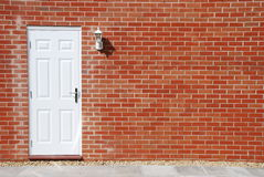 Puerta blanca en una pared de ladrillo imagen de archivo