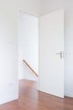 Puerta blanca, piso de madera abajo a la escalera en el hogar moderno, estilo minimalista Imagen de archivo