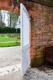 Puerta blanca a un jardín fotos de archivo
