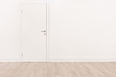 Puerta blanca y un suelo de parqué marrón claro Foto de archivo