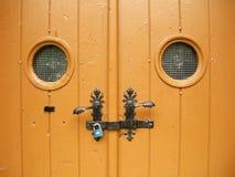 A puerta cerrada con dos redondeó pequeñas ventanas Imagenes de archivo