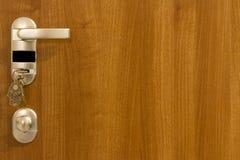 A puerta cerrada con llaves en el ojo de la cerradura imagen de archivo