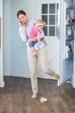 Puerta cerrada del refrigerador de la mujer mientras que lleva al bebé Foto de archivo