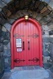 A puerta cerrada rojo en un edificio fuerte construido con la pared de piedra fuerte foto de archivo libre de regalías
